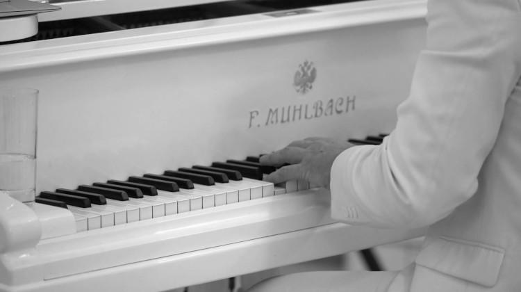 Парень играет за белым роялем
